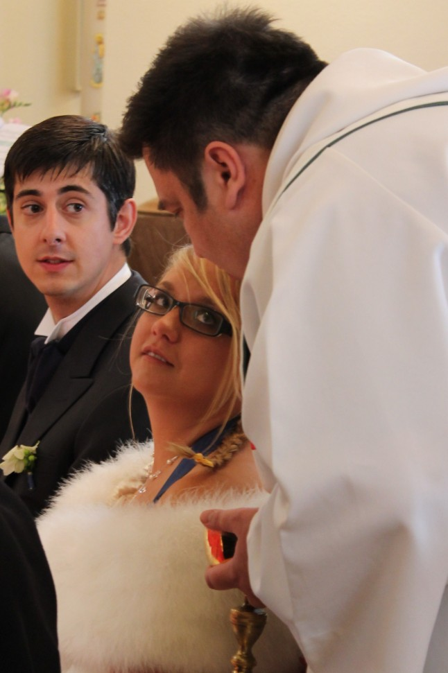 prêtre penché vers les mariés