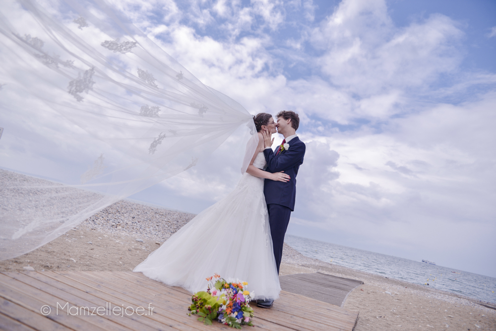 Photo de couple sur la plage, le voile volant au vent / Photo : Mamzelle Joe