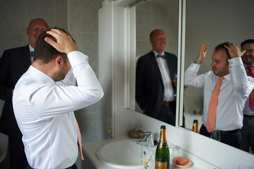Habillage du marié entre hommes et avec du champagne ! // Photo : Stephane Evras