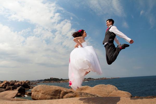 Mariage rose et blanc mariés saut mer