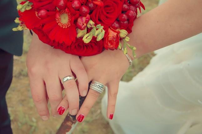alliances des mariés et bouquet rouge
