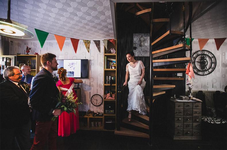 Découverte des mariés dans l'escalier dans la maison décorée de fanions multicolores