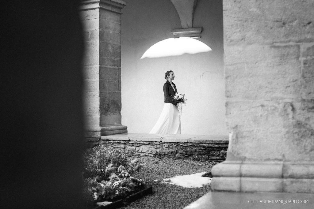 La mariée marche songeuse dans le cloître
