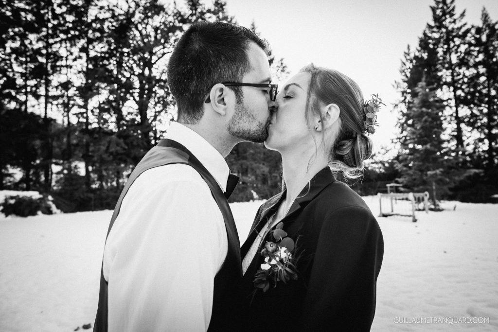 Les mariés s'embrassent dans la neige
