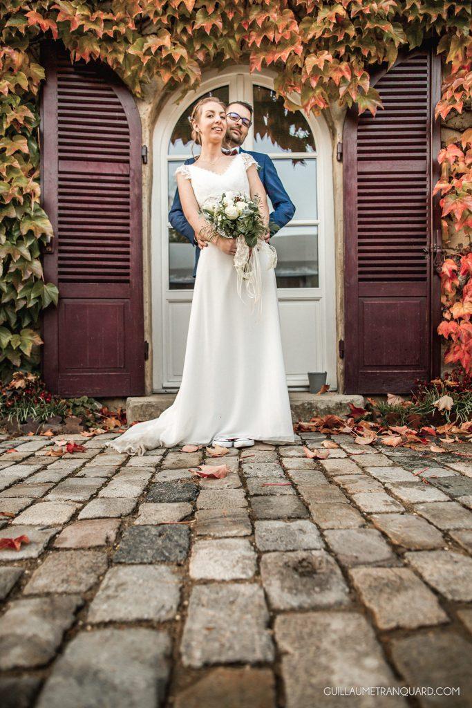 Couple de mariés devant les feuilles d'automne