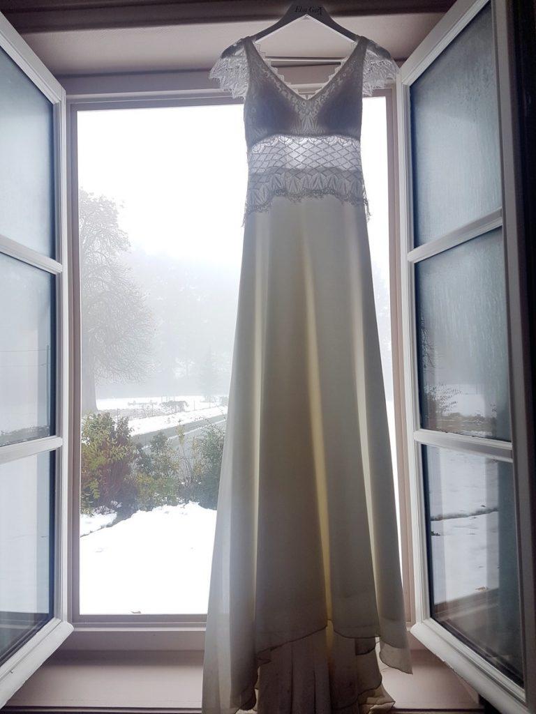 Robe de mariée pendue à la tringle de la fenêtre