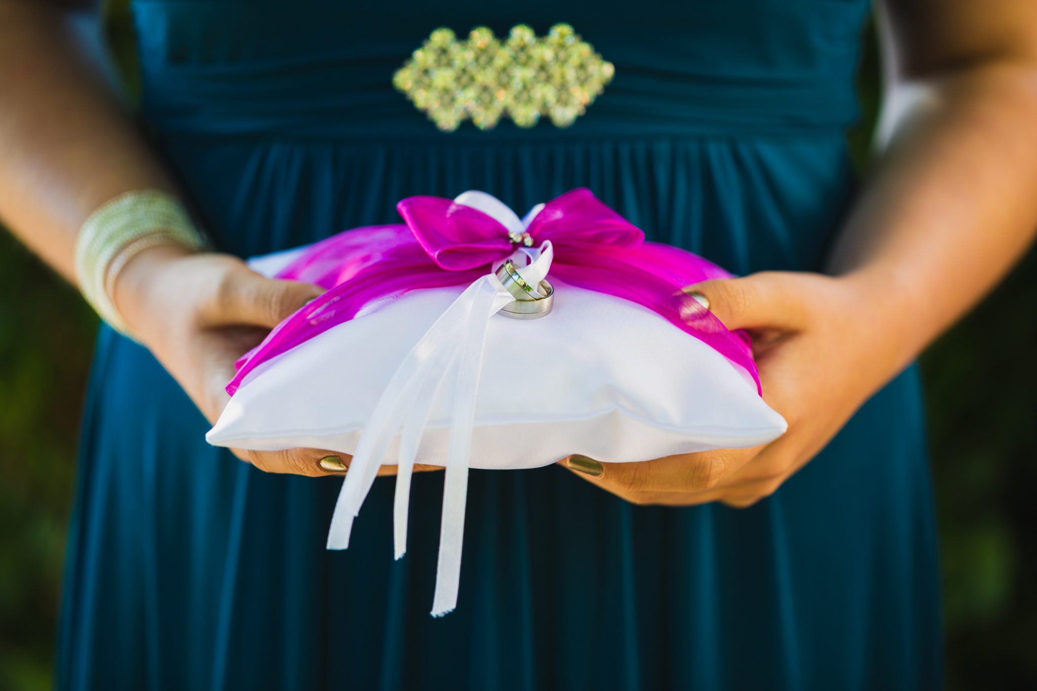 Female hands holding wedding rings on a cushion
